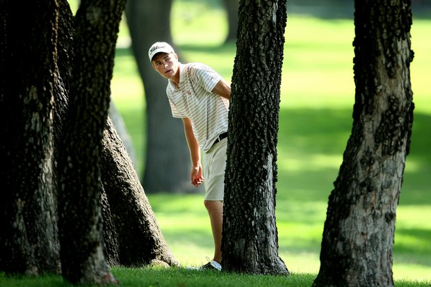 Drew Kittleson looks over his options after his tee shot landed in a cluster of trees.