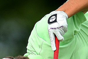 "Travis Woolf has written on his glove ""Pray & Work"" as he tees it up at No. 10."