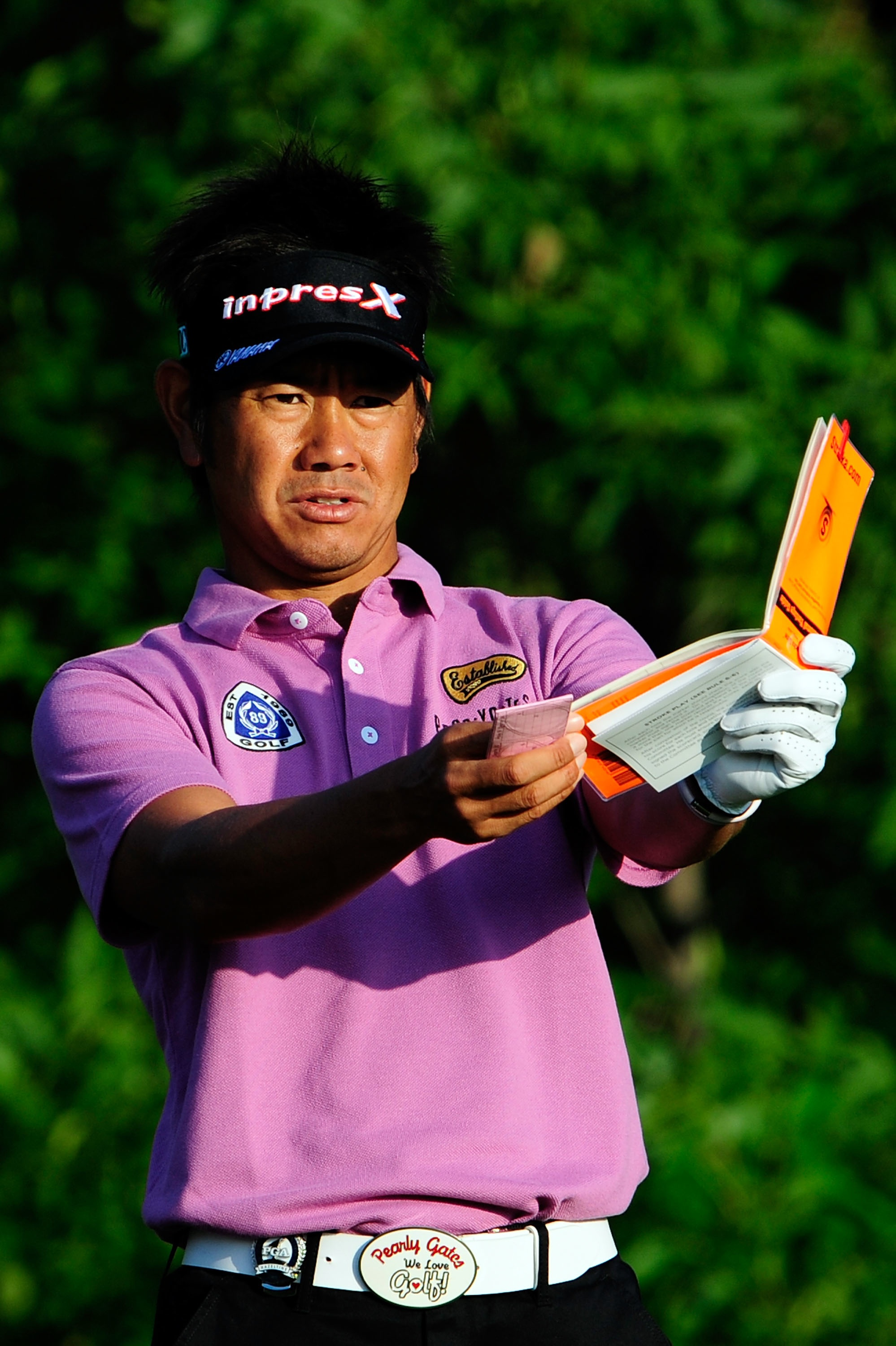Hiroyuki Fujita of Japan checks his yardage book on the 10th tee during the first round.