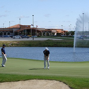 Players practice on the 10th green at Blue Top Ridge. Behind them is the adjacent Riverside Casino.