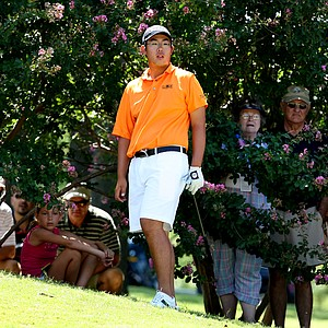 Byeong-Hun An watches his shot at No. 8 while spectators peek through the bushes in the afternoon round.