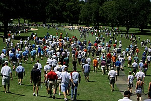 Spectators walk down the fifth fairway during the afternoon round.