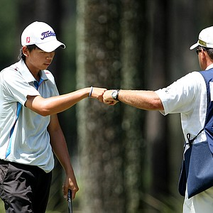 Chien Yao Hung, left, gets a fist bump from his caddie at No. 12.