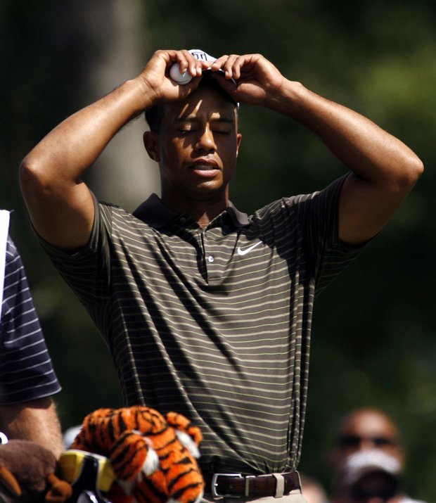 Tiger Woods reacts to his bogey on the 11th hole while waiting to tee off on the 12th hole during the third round of the Deutsche Bank Championship golf tournament in Norton, Mass.