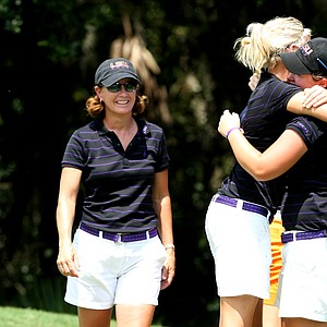 LSU head coach Karen Bahnsen, left, watches as her players Amalie Valle, center, and Mary Michael Maggio hug after defeating Auburn and winning the Hooters Collegiate Match Play Championship.