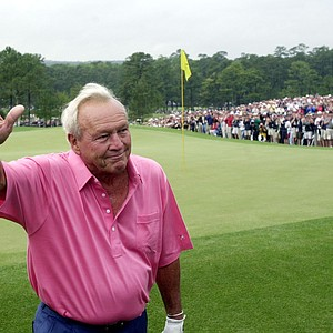 Four-time Masters champion Arnold Palmer waves to the gallery after completing the second round during his final Masters on April 13, 2002. (AP Photo/Dave Martin)