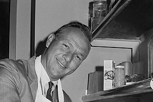 Arnold Palmer dons an apron Feb. 13, 1964 as a gag to say he has added a New York laundry and dry cleaning business to his mushrooming enterprises in New York City. (AP Photo/John Rooney)