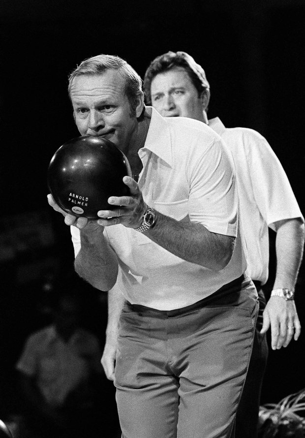 """Arnold Palmer in the finals of the """"Dynamic Duos"""" bowling competition, Dec. 17, 1977 in Las Vegas. In background is his bowling partner, golfer Ray Floyd. They lost by six pins to the team of former football stars Jim Brown and Jim Taylor. (AP Photo/Wally Fong)"""