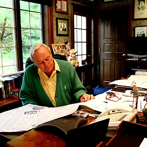 Arnold Palmer reads the newspaper in his office in Latrobe, Pa.