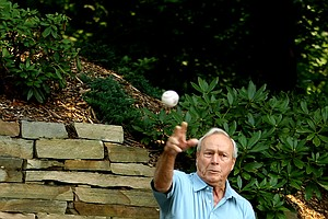 Arnold Palmer practices his throwing skills outside his office for an upcoming baseball engagement as part of his 80th birthday celebrations.