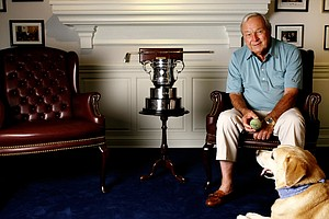 Arnold Palmer in his trophy room with his dog Mulligan.