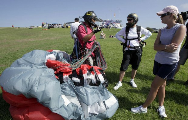 Paraglider pilot Keith Huong gives instructions to Catriona Mathew, center, and Paula Creamer following the third round of the LPGA Samsung World Championship at Torrey Pines.