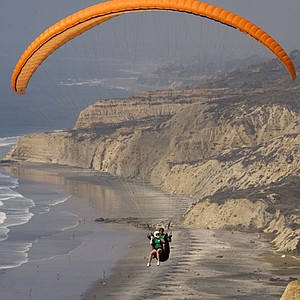 Brittany Lincicome (front, green helmet) rides on a tandem paraglider with pilot John Ryan after the third round of the LPGA Samsung World Championship at Torrey Pines.