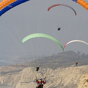 Angela Stanford (front, yellow helmet), waves as she rides on a tandem paraglider with pilot Steve Stackable following the third round of the LPGA Samsung World Championship at Torrey Pines.