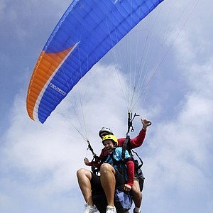 Angela Stanford (front, yellow helmet), and pilot Steve Stackable soar off the edge of a cliff in a tandem paraglider following the third round of the LPGA Samsung World Championship at Torrey Pines.
