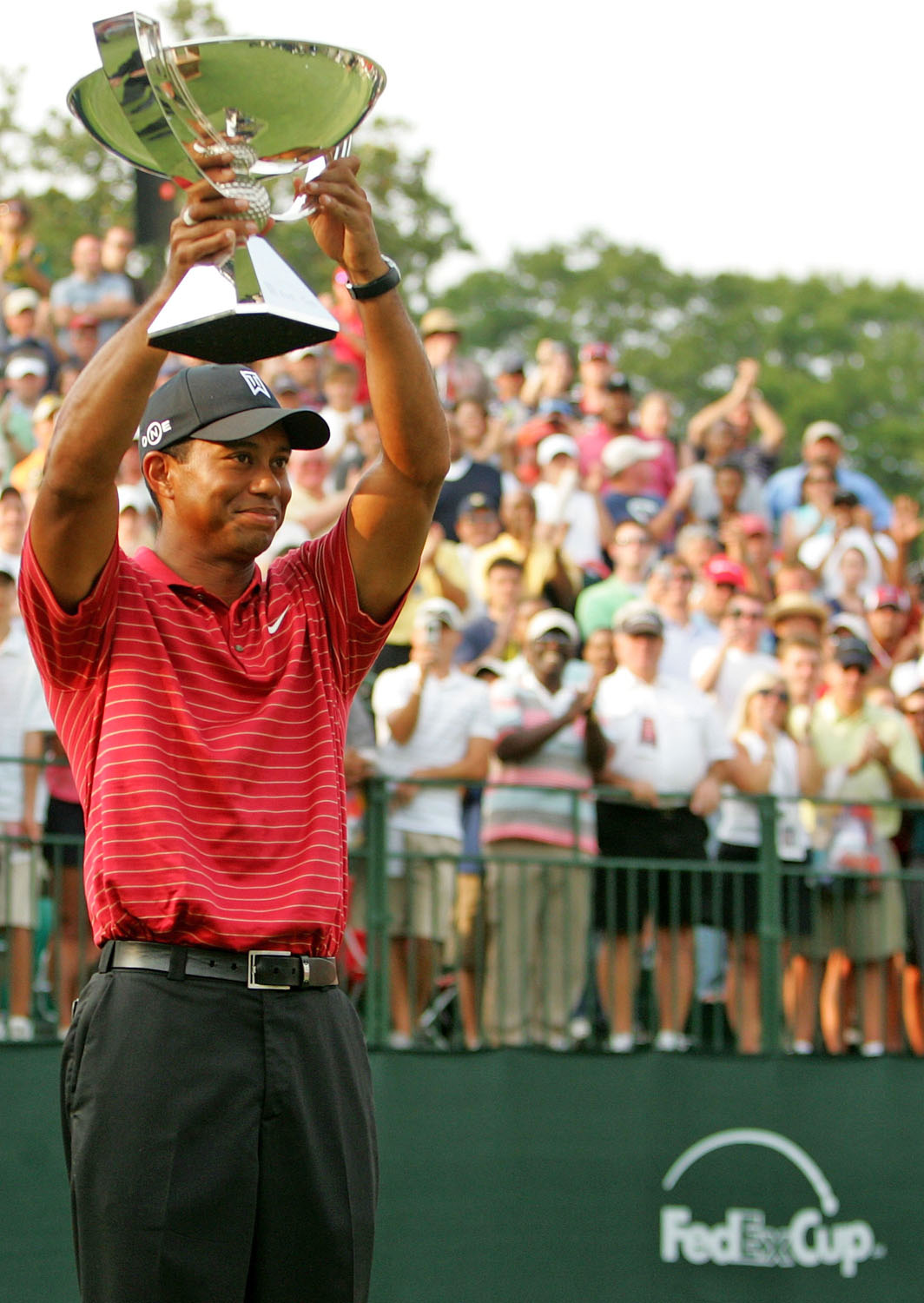 Tiger Woods holds the FedEx Cup after winning the Tour Championship in 2007.