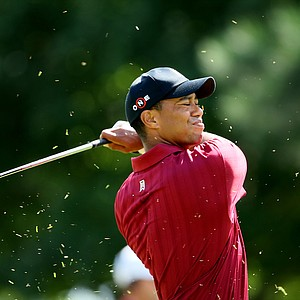Tiger Woods closes his eyes to avoid the spray of grass at No. 1.
