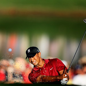 Tiger Woods chips out of a bunker at No. 18.