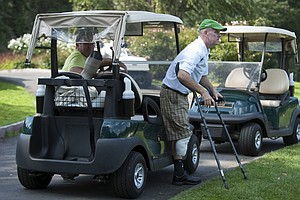 Ken Green, right, prepares to walk from a golf cart at a charity golf tournament at Ridgewood Coutry Club in Danbury, Conn. The Friends of Ken Green Benefit Tournament is raising money for the Ken Green Living Expenses Trust. Contributions can be made to the Ken Green Trust. For more information, visit www.kengreenscomeback.com.
