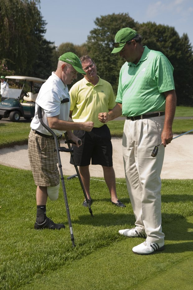 Phil Blackmar, right, gives a fist bump to Ken Green, left, during a charity golf tournament at the Ridgewood Country Club. Contributions can be made to the Ken Green Trust. For more information, visit www.kengreenscomeback.com.