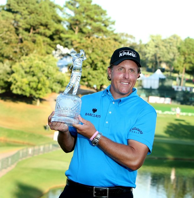 Mickelson hoists the Tour Championship trophy while wearing his cutting-edge polo shirt.