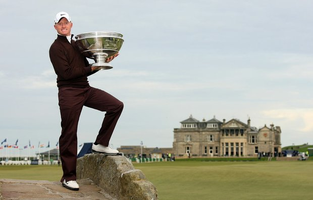Simon Dyson holds the trophy aloft on the Swilcan Bridge on the 18th hole after his victory at the The Alfred Dunhill Links Championship at The Old Course at St. Andrews.