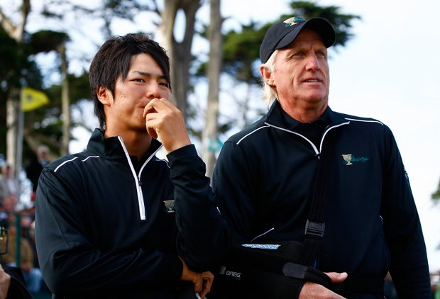 Ryo Ishikawa and International team captain Greg Norman wait on the 18th green.