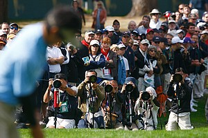Ryo Ishikawa of the International Team lines up a putt on the first green amid a sea of photographers.