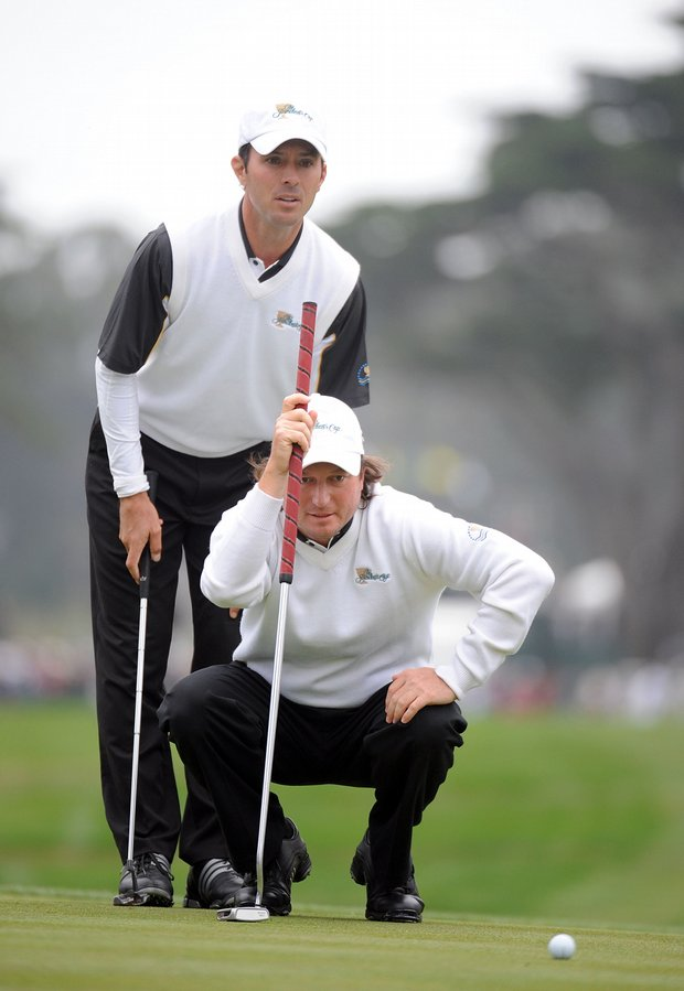 Tim Clark and Mike Weir of the International Team line up a putt during the Saturday's morning foursome matches.