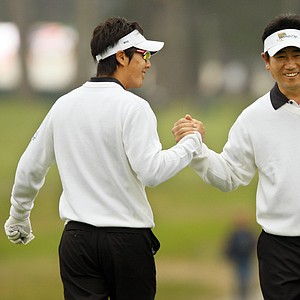 International players Ryo Ishikawa, left, congratulates partner Y.E. Yang after Yang hit his approach close to help win the first hole of their foursomes match.
