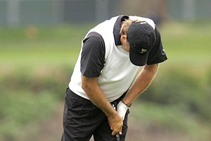 International player Retief Goosen reacts to a wayward shot from the 14th fairway during his foursomes match.