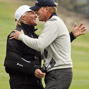 International captain Greg Norman, left, greets Team USA's Steve Stricker after Stricker won the 10th hole with a birdie during his four-ball match.