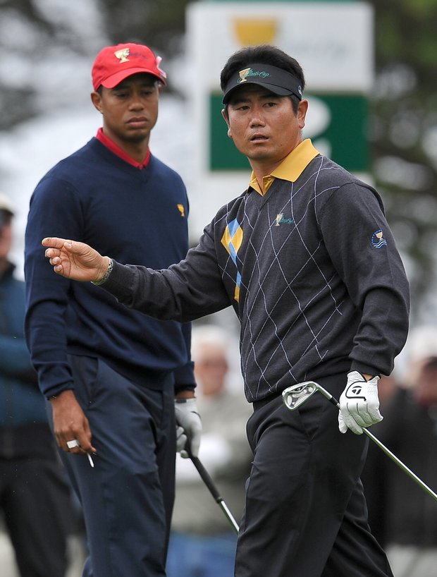 Y.E. Yang watches his tee shot on the second hole as Tiger Woods looks on.