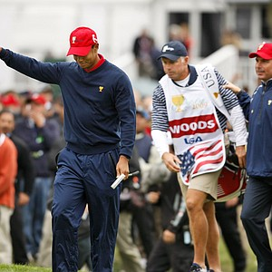 Tiger Woods is followed by caddie Steve Williams and Fred Couples after Woods won his singles match against Y.E. Yang, 6 and 5.