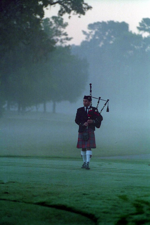 Walking through the early morning fog on the first tee Oct. 28, 1999, bagpiper Steve Agan begins the memorial service for Payne Stewart before the PGA Tour Championship at Champions Golf Course in Houston.