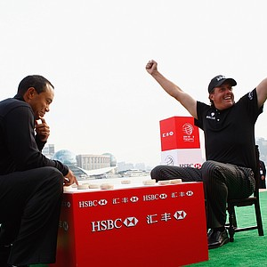Phil Mickelson celebrates while playing a game of Chinese chess with Tiger Woods during the Official 2009 WGC-HSBC Photocall at the Shanghai Port International Cruise Terminal on November 3, 2009.