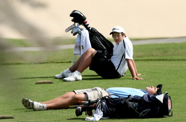 Jonathan DiIanni (laying down) and Andrew Vu wait on No. 18 tee.