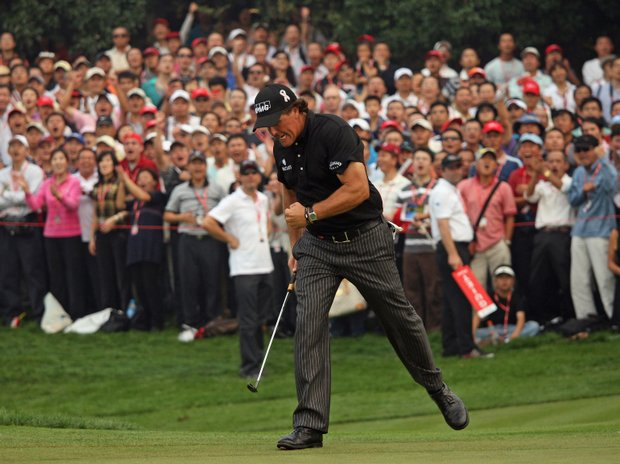 Phil Mickelson celebrates a par putt on the 16th green during the final round of the WGC-HSBC Champions.