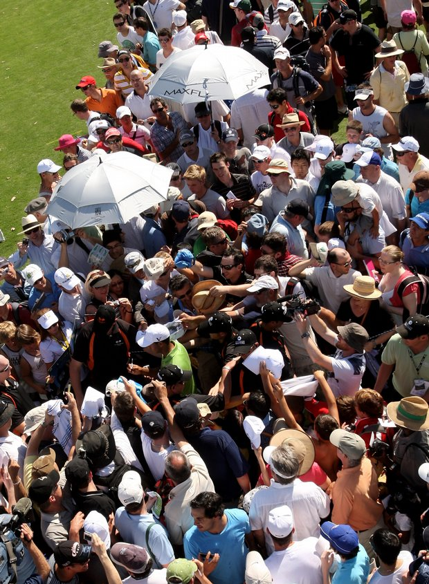 Tiger Woods signs an autograph as he leaves the 18th hole during a practice round for the Australian Masters.
