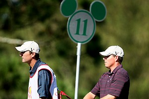 Justin Leonard and his caddie leave the 11th tee. Leonard is in a four-way tie for the lead.