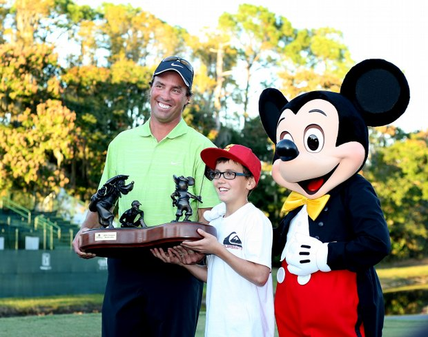 Stephen Ames poses with his son, Ryan, 10, and Mickey Mouse after winning a playoff at the Children's Miracle Network Classic.