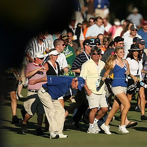Crowds run through the fairway at No. 18 to see the end of regulation play at the Children's Miracle Network Classic.