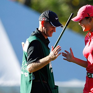 Michelle Wie is congratulated by her caddie, Brenden Woolley, after hitting her sand shot to 6 inches on the 18th green at the Lorena Ochoa Invitational.