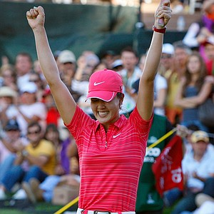 Michelle Wie raises her arms after winning the Lorena Ochoa Invitational, her first LPGA victory.