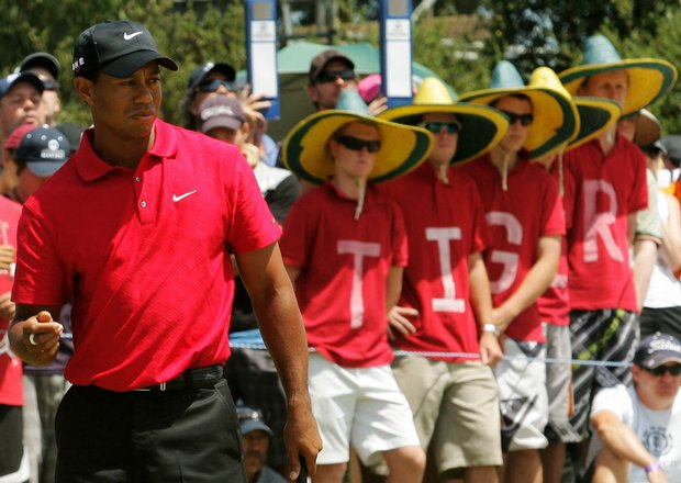 Fans watch Tiger Woods putt on the first hole during the final round of the Australian Masters.