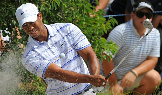 Tiger Woods plays out of a bunker during the third round of the Australian Masters.