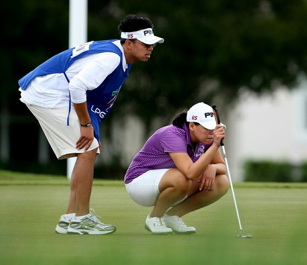 Dorothy Delasin, with her caddie's help, lines up a putt at LPGA Q-School.