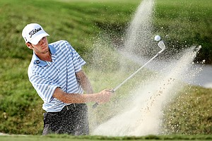 Troy Merritt blasts out of a greenside bunker at No. 18 on the Lakes Course.