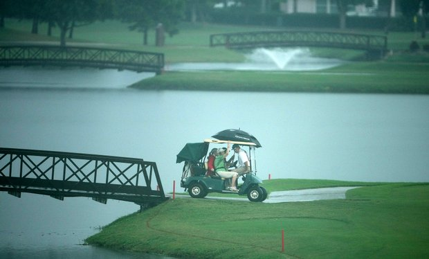 Golfers are brought back to the clubhouse after play was suspended due to weather during Friday's round.