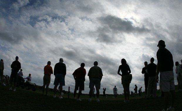 Spectators watch golfers on the practice range before Sunday's fifth round.